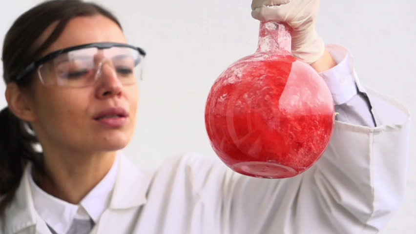 Female scientist mixing chemicals in flask