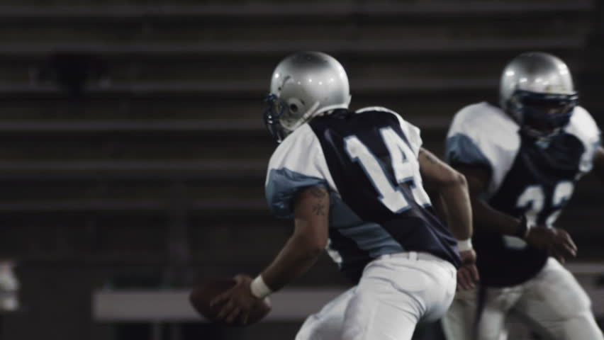 A football player runs with the ball while players trying to tackle him miss | Shutterstock Video #4706216