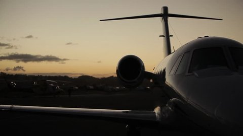 Left to right pan shot of a Cessna Citation IV jet aeroplane grounded at dusk. Shot on a Canon 5D MK II with a Zeis 50mm f1.4 prime lens.