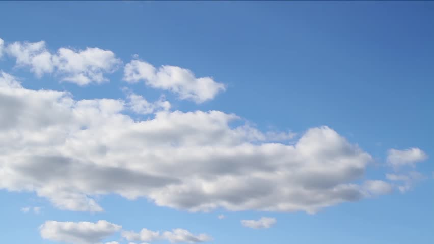 Beautiful white clouds soar across the screen in time lapse fashion over a deep blue background. 30 second loop. #4718921