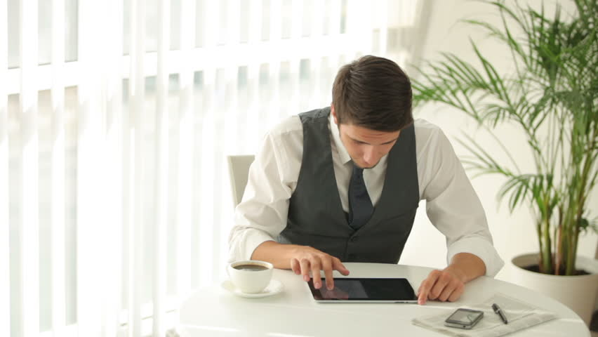 Good-looking man sitting at table and using touchpad