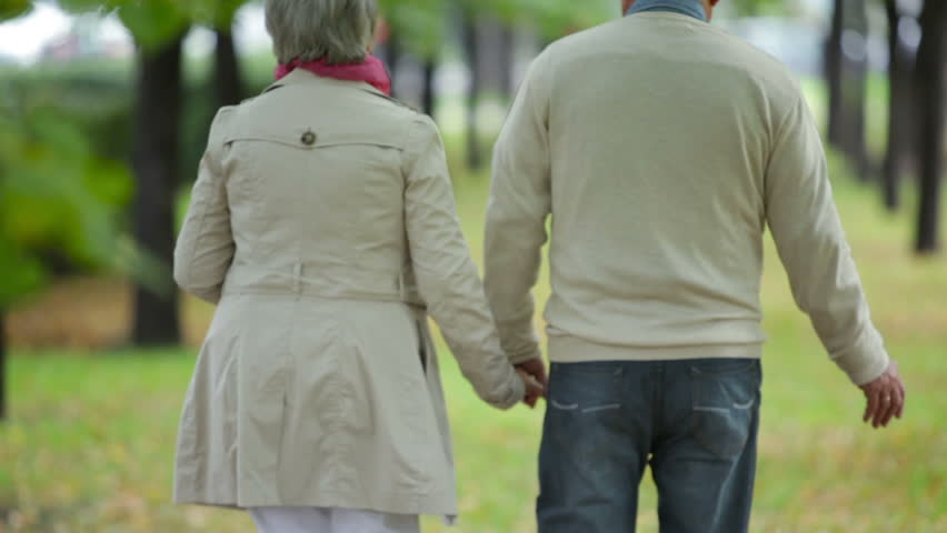 Senior couple taking an unhurried walk along the park lane | Shutterstock HD Video #4728758