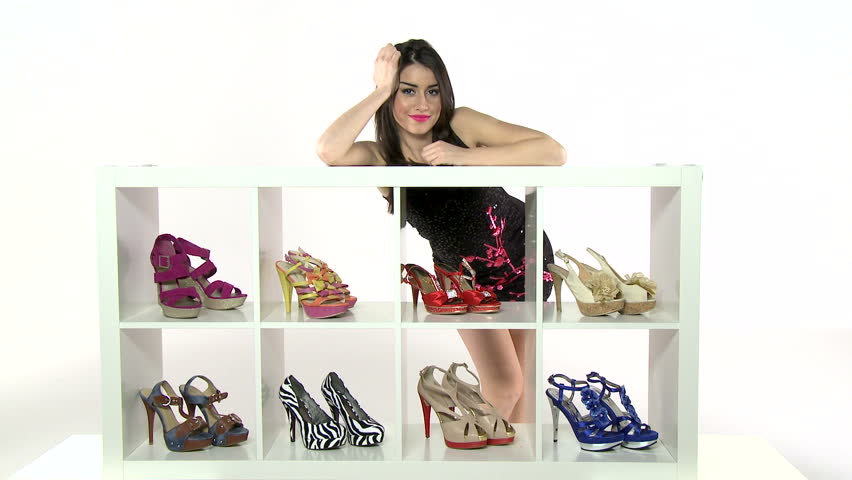 Beautiful woman posing with her shoes in a closet. High definition video shot on white studio background.