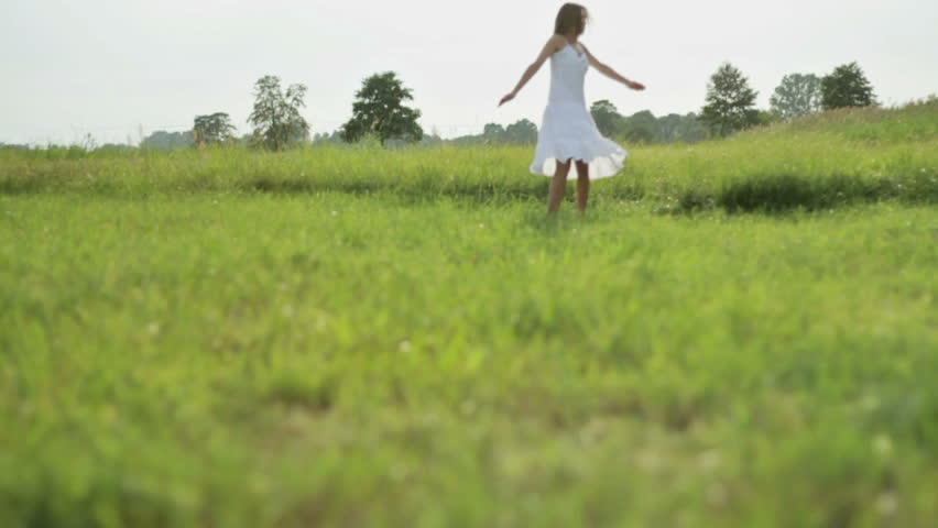 Young girl dances outdoors in a green meadow during sunset, slow motion