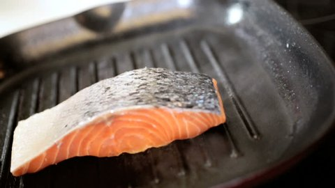 Fresh Sockeye salmon steaks being placed on a hot griddle to cook close up