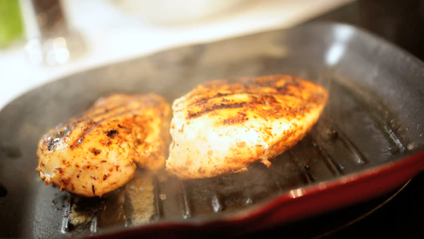 Close up of organic white meat chicken being char grilled in a griddle pan