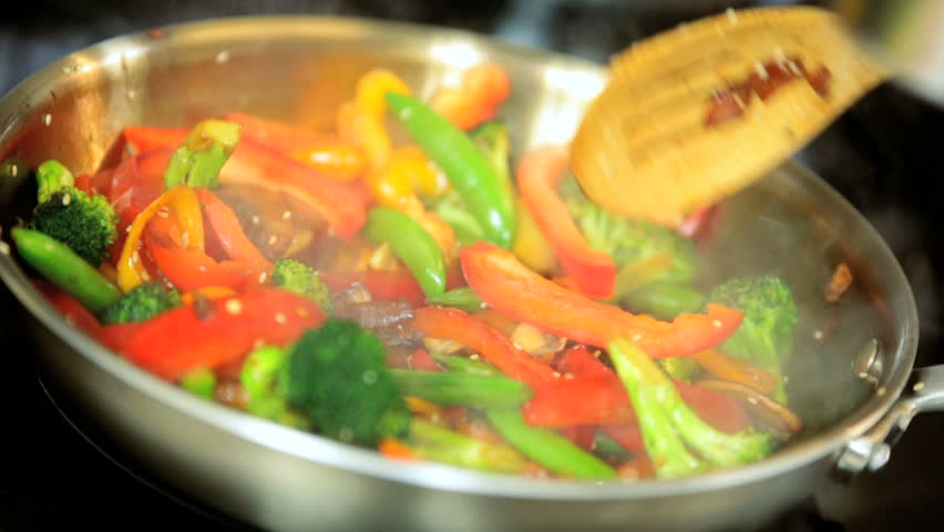 Close up of a pan fry meal of delicious broccoli, mushrooms, peppers, and peas for a colorful vegetarian stir fry meal