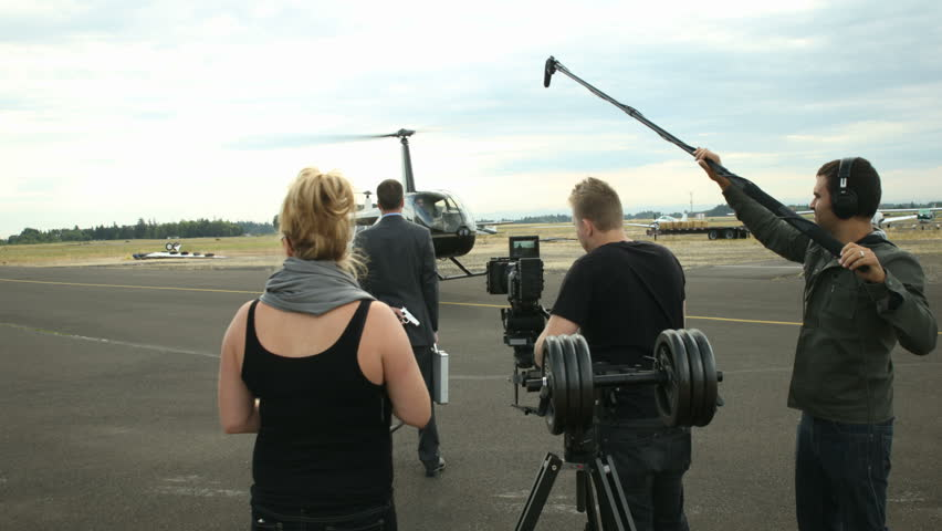 Behind the scenes, crew shoots helicopter landing by businessman