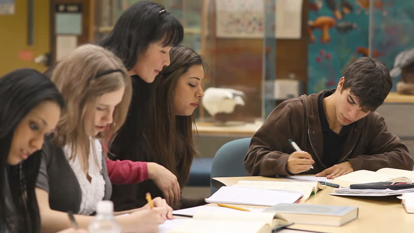 a college professor helps students understand a chemistry  a group of college students study their books and notes in class hd stock footage