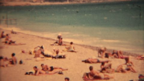 LES BAINS EUROPE CIRCA 1963: Lido Les Bains Beach bikinis vintage film. People on beach,surf boards, swimsuits and bikinis. Men in Speedo wear. Travel and fun historical view.