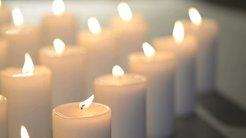 Dolly Shot Of White Candles Burning With Soft Candle Light. Front Candles In