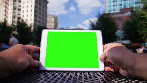 A man uses a tablet computer outside at Market Square in downtown Pittsburgh Pennsylvania.  Green screen and corner markers included for advanced motion tracking.