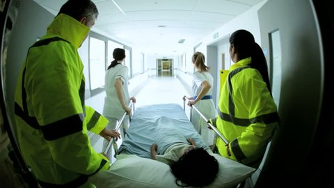 Wide angle view of paramedics rushing an injured child patient into a hospital for emergency critical treatment