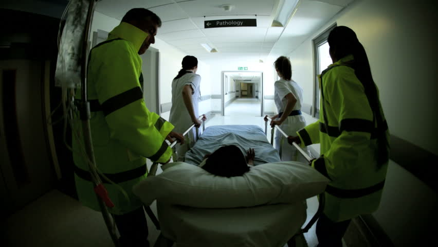 Wide angle view of paramedics rushing child patient to critical care center for emergency treatment after accident