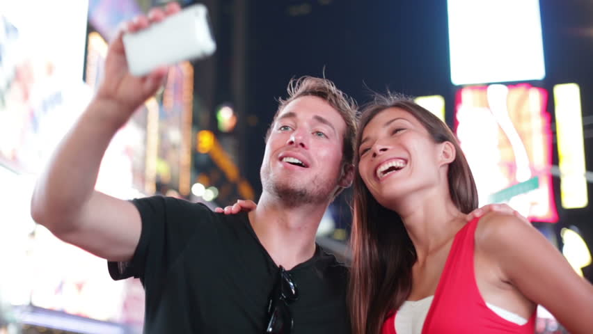 Dating young couple happy in love taking self-portrait photo on Times Square, New York City at night. Beautiful young multiracial tourists having fun date, Manhattan, USA. Asian woman, Caucasian man.