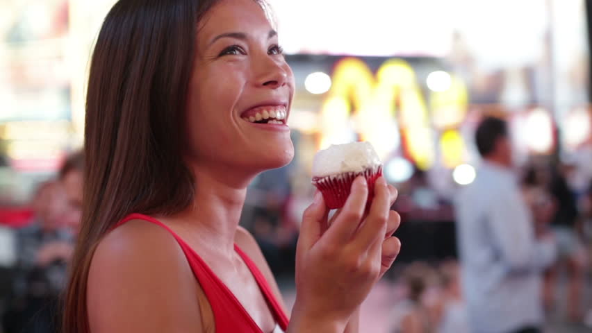 Woman eating cupcake in New York on Times Square, Manhattan. Cute girl eating unhealthy cupcakes food smiling happy. Beautiful woman in New York City at night having fun, Mixed race Asian model.