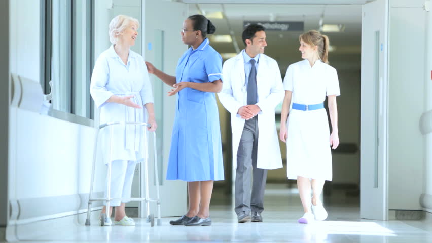 Doctor and nurses talk with elderly female patient about recovery and physical therapy after procedure | Shutterstock HD Video #4820798