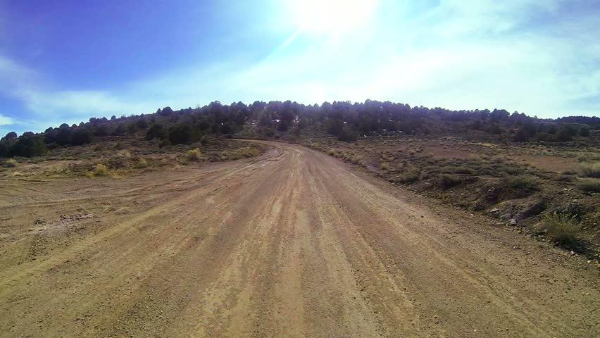 POV shot driving along a dirt road.