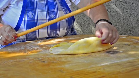 Italian Chef rolls pizza dough Old traditional way - Stock Video. -Uberstock- HD 1080p- A Chef rolls dough to flatten it on wooden table. Close up Wide Shot.