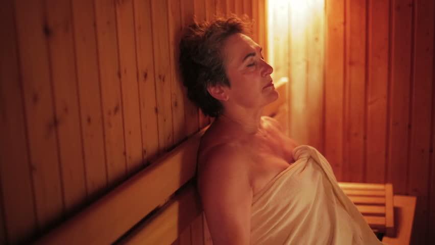 Sexy senior woman relaxing inside a fancy sauna