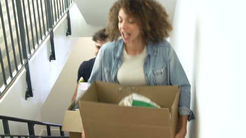 Couple carrying boxes up stairs as they move into new home