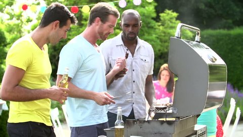 Three men cooking on barbecue and toasting beer bottles in backyard