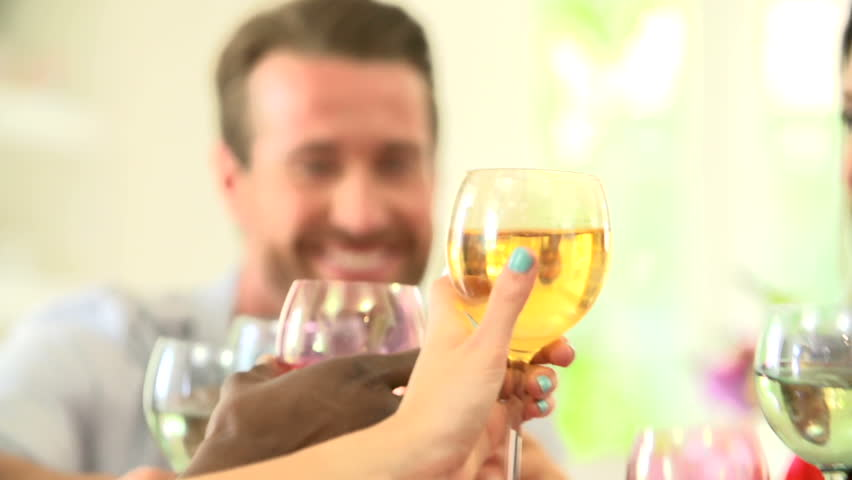 Close up view of friends toasting wien glasses together at dinner party slow motion view
