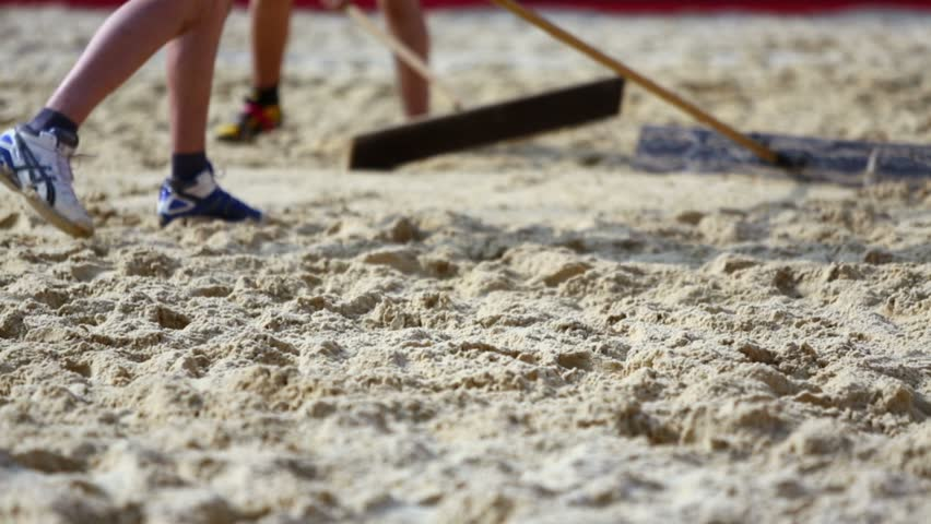 People flatten sand surface at beach volleyball pitch by wooden tools at sunny day during competition