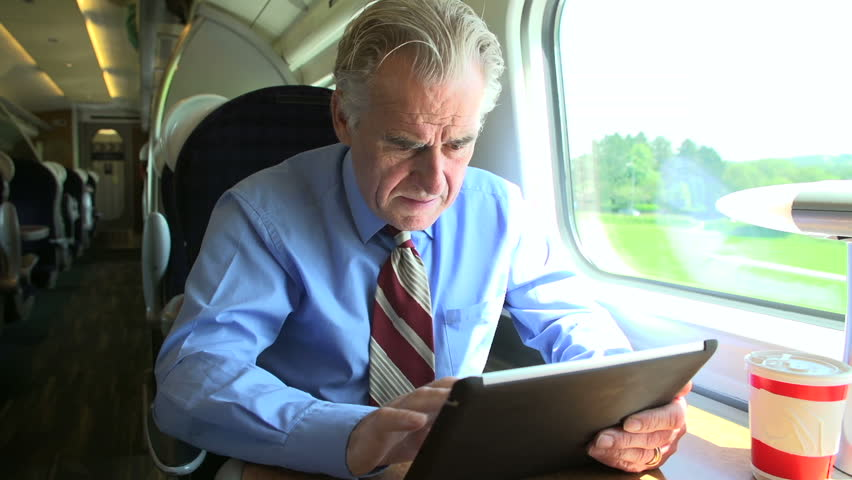 Close up of a senior businessman working on a digital tablet on a morning train commute