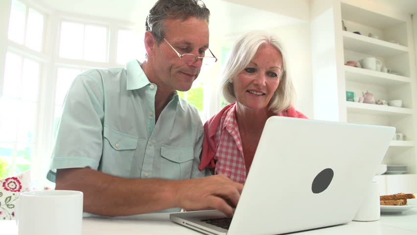Happy middle aged couple looking at laptop and talking in the morning