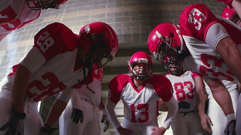 A team of football players huddle in a group and clap to get hyped and ready for the game to start