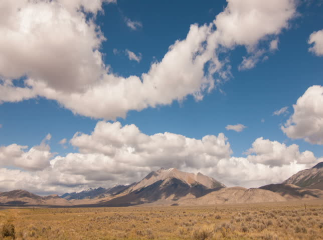NTSC - Time lapse clouds travel over plains and mountains. #4892468