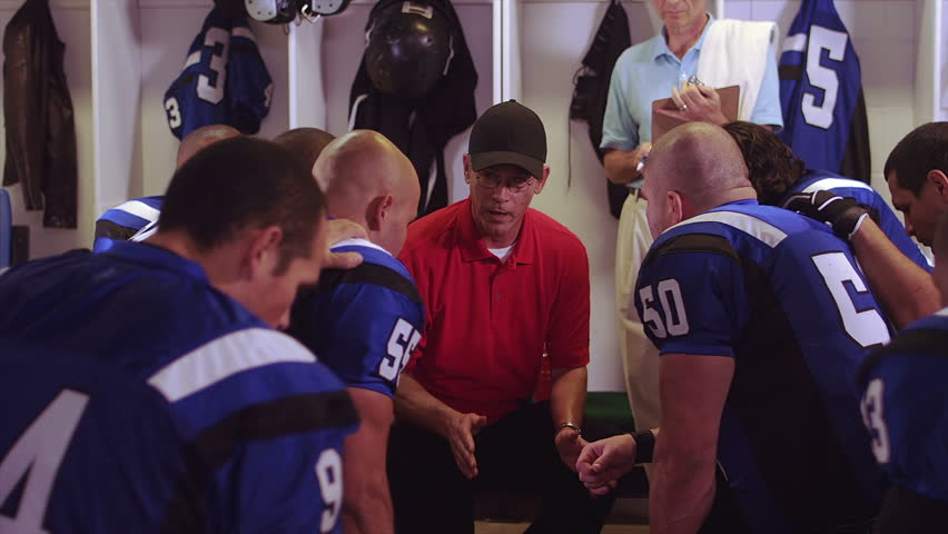 Football players sit in a circle in the locker room and get a speech from their coach before a game