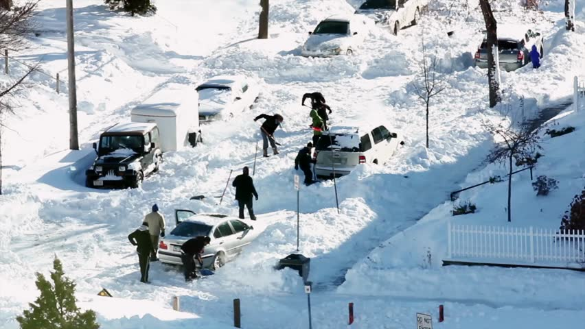 People digging cars out of snow after a blizzard.