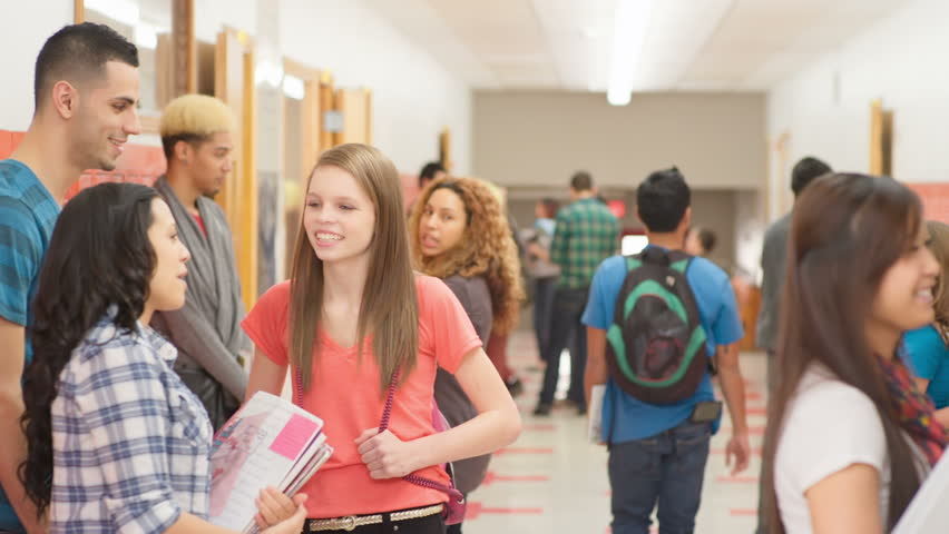 a group of friends stand in the hallway talking before
