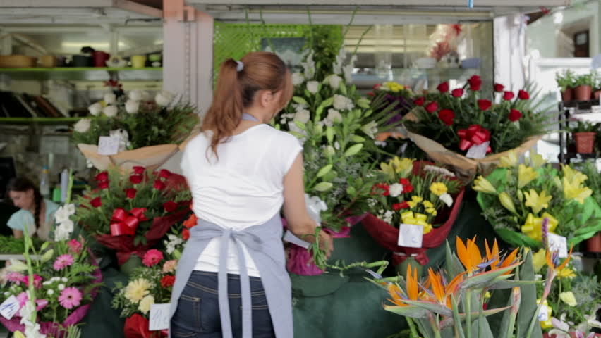 Rear view of an attractive florist business woman owner getting ready for work, tying up her apron, picking and showing with pride a bouquet of sunflowers, smiling outdoors.