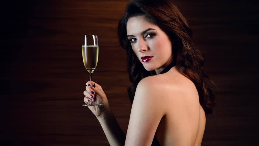 Sexy woman holding champagne glass in cocktail dress - available in 4k