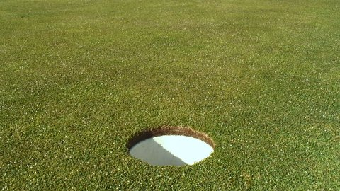 A close up of a golf ball rolling into a hole.