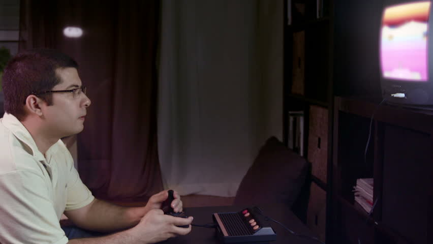 A young adult plays an old video-game / A young man plays energetically an old video game, sitting in his living room.