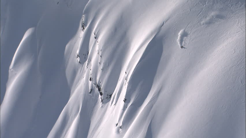Skier charging down a perfect powder covered face with a bluebird sky. | Shutterstock HD Video #4928669