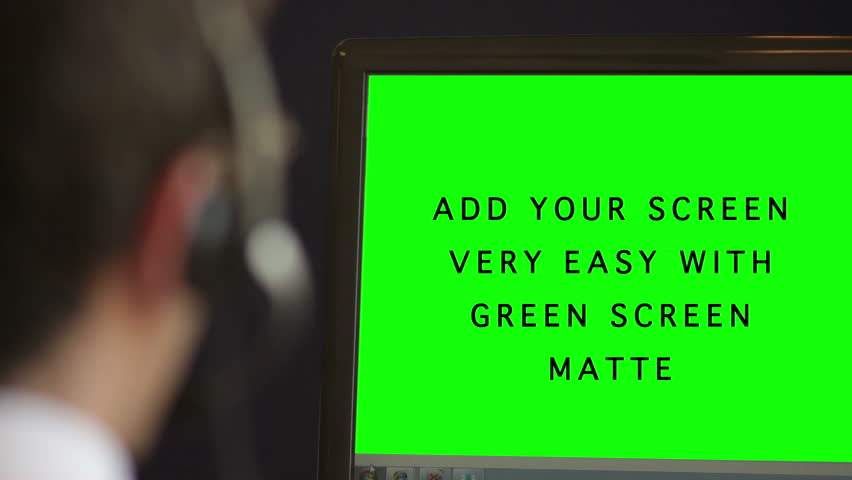 Man in Call Center with Alpha Green Screen. Young man opeator with headset talks to a customer while looking at her computer monitor. You can add your graphic, picture or video on the computer monitor