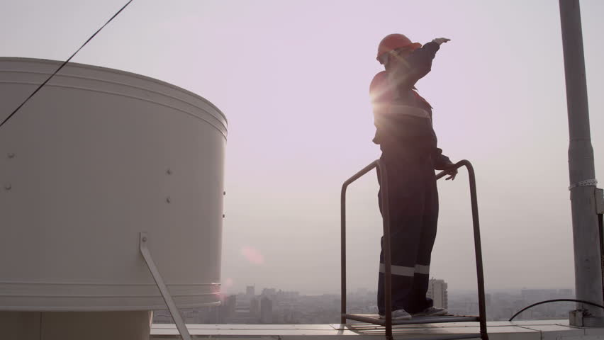 Worker in helmet climbs stairs to the roof