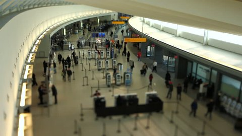 Airport travelers at check in area using a tilt shift lens.