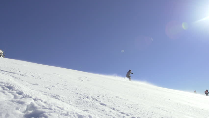 Slow Motion Wide Shot Of A Professional Skier Skiing Downhill On A Steep Terrain