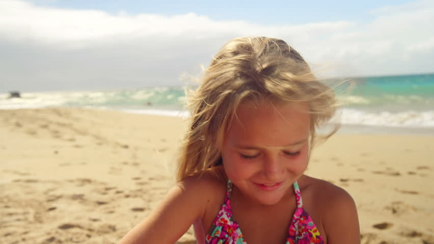 A young girl sits in the sand at the beach and plays a ukulele
