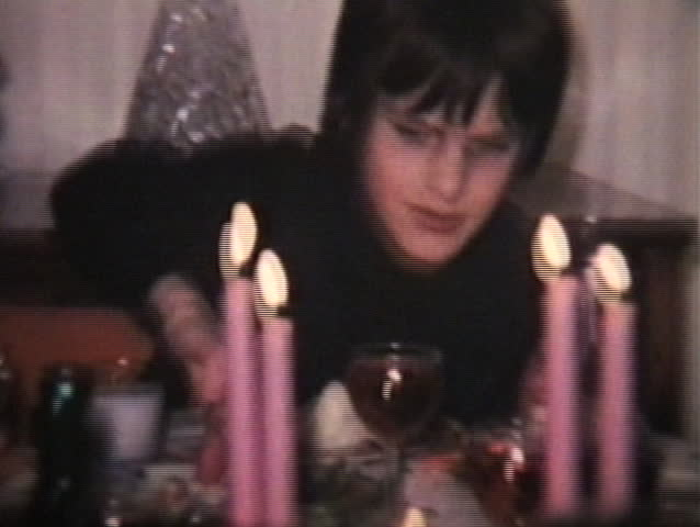 Two brothers making crazy faces at the camera at a family dinner. (1974 - Vintage 8mm film footage)