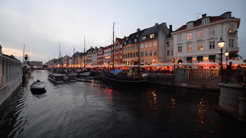 COPENHAGEN, DENMARK - SEPTEMBER 14, 2013: Boats pass through the Nyhavn Canal. The 17th century canal is lined with historic ships and the waterfront with restaurants and cafes.