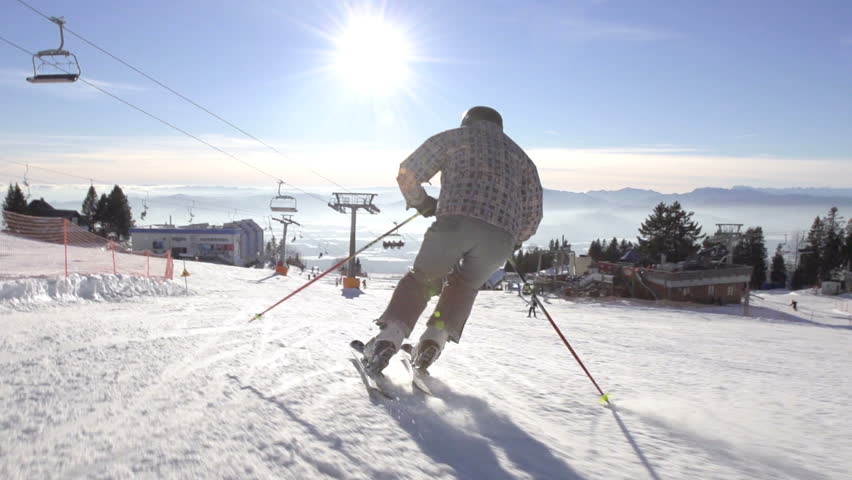 Slow motion rear view of skier skiing down the snowy slope