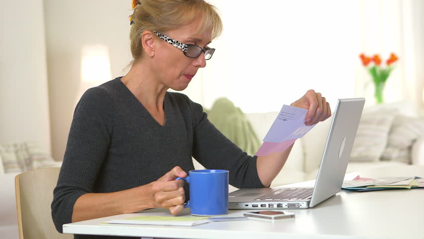 Middle aged woman drinking coffee and using laptop to pay bills