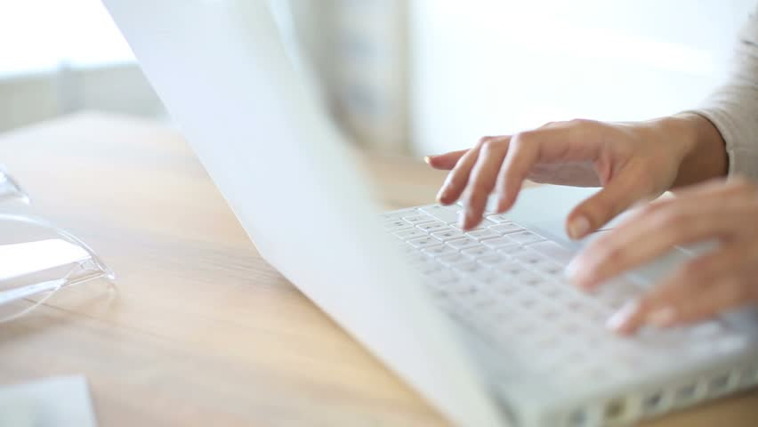 Woman's hand typing on laptop keyboard